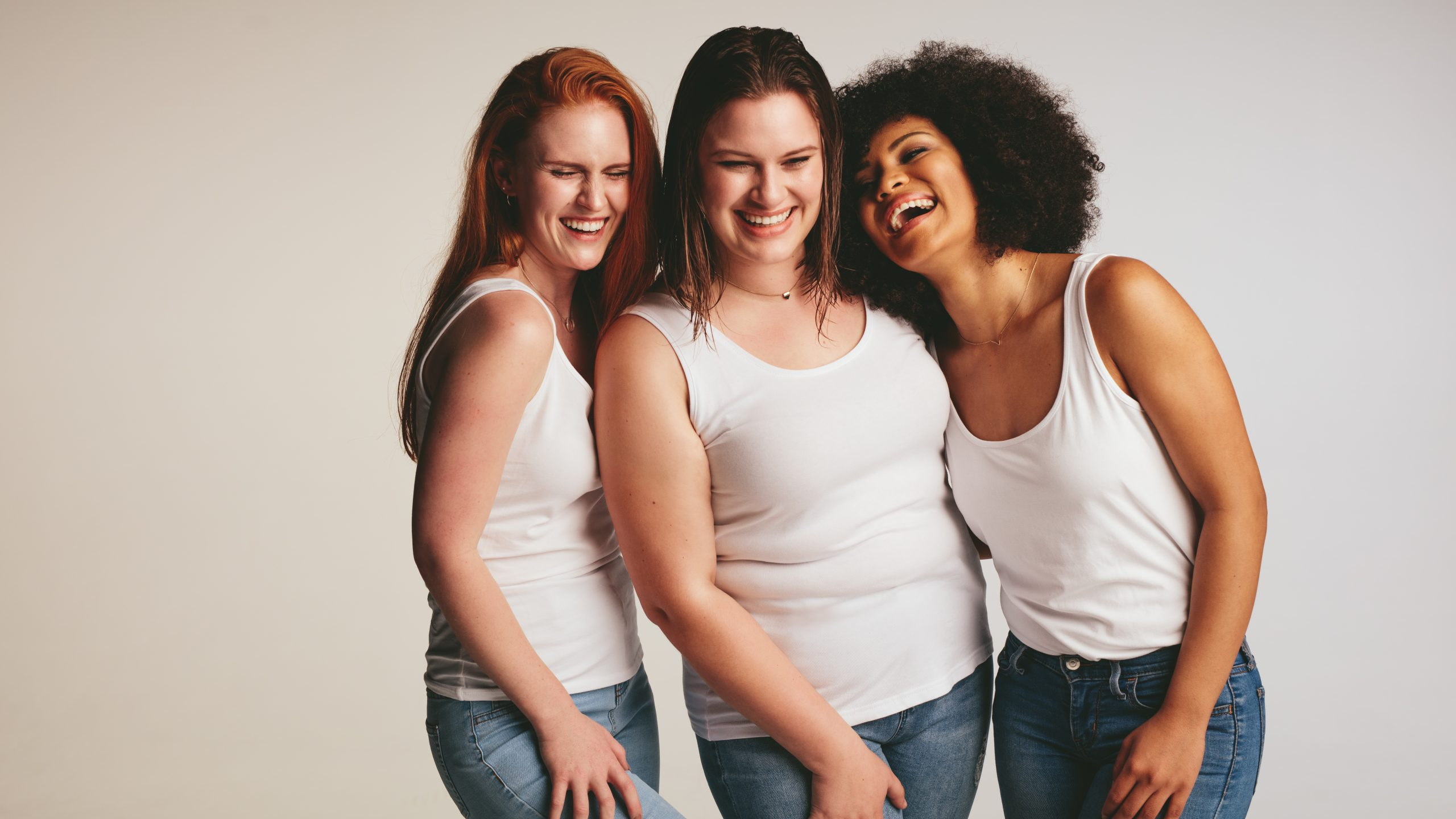 Three women of different races laughing together in white tshirt and jeans
