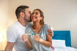 Young couple is happy because of positive pregnancy test