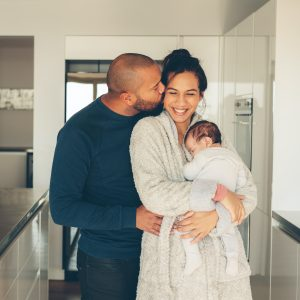 Man kissing his wife holding a newborn baby boy in kitchen